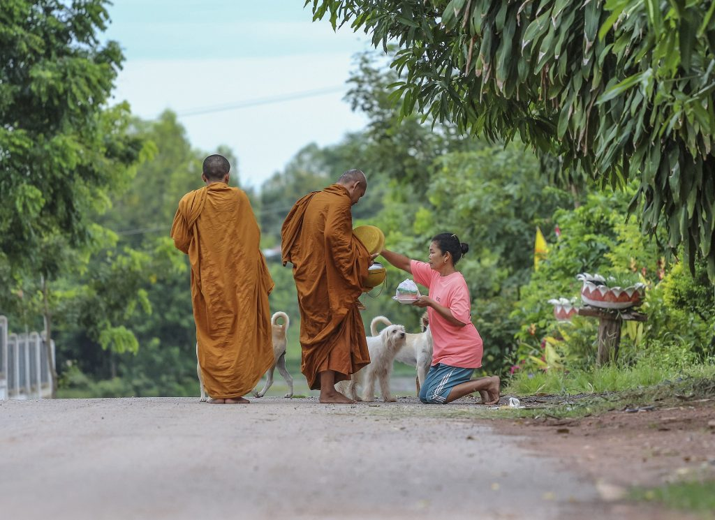 Woman making merit by giving offerings to monks in Thailand