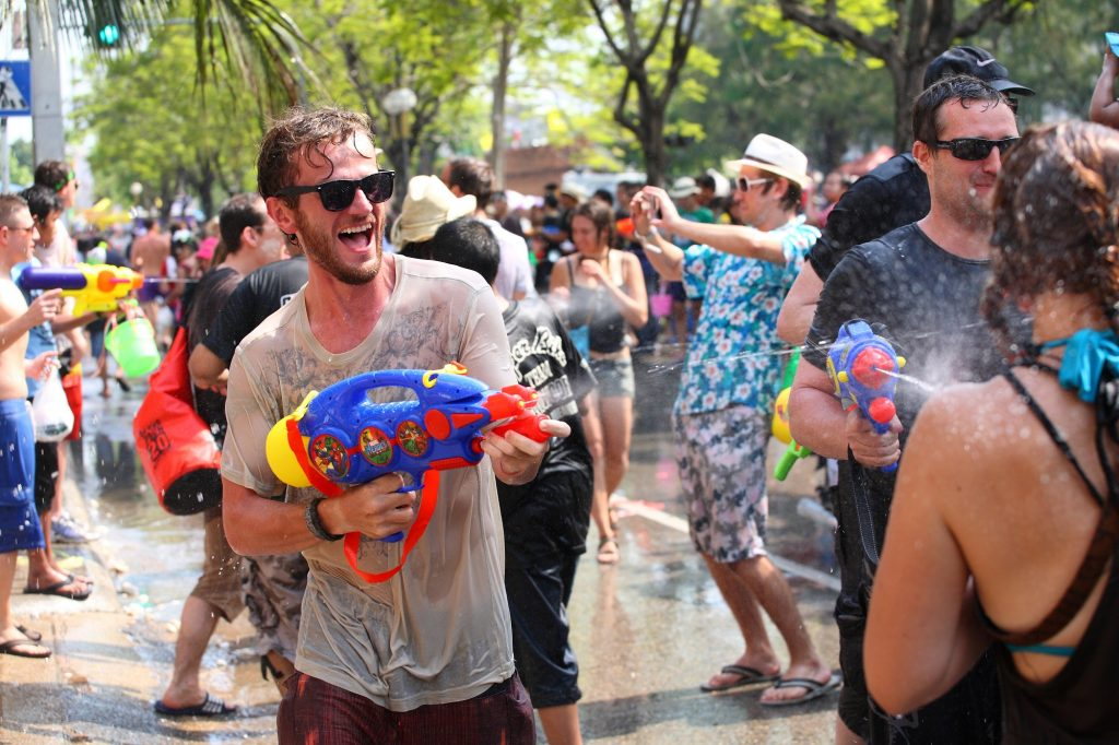 A happy tourist spraying a water gun during Songkran festival, Thailand
